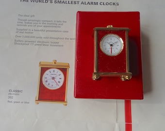 "Swiss Made Nepro transistorized alarm mini clock in Gilt tone with "" red lacquer"" front."