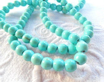 A set of 12 6 mm synthetic TURQUOISE beads.