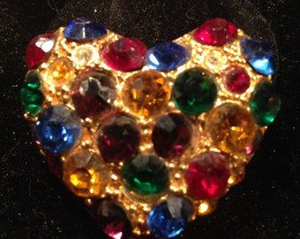 Gold heart shaped brooch with many different brightly colored rhinestones