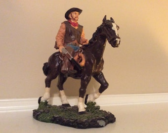 Cowboy Riding a Horse with His Rifle in His Hand.