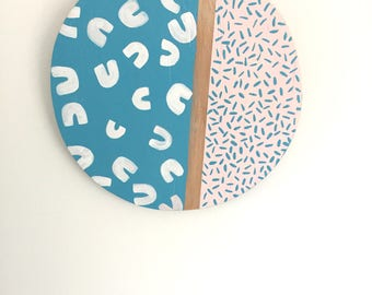 Abstract doughnut and confetti style pattern painted on plywood circle
