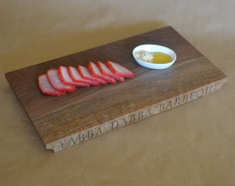 "YABBA DABBA BARBEQUE sale priced is laser-engraved on one edge of this figured Oregon black walnut serving board measuring 14"" x 7 3/8"" x 1"""
