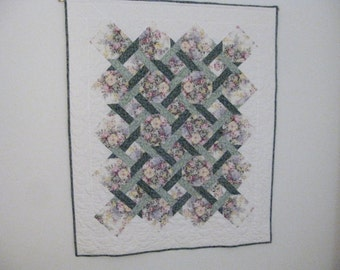 Handmade floral lattice quilt in greens and floral prints which can be a wallhanging.