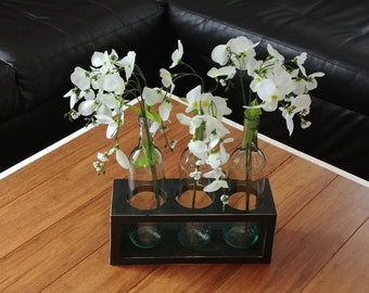 Black wood centerpiece with wine bottle vases