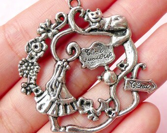 a silver pendant, alice in Wonderland
