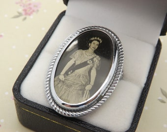 A 1950s hand made Queen Elizabeth II vintage jewelry brooch showing the young Queen in formal dress. Made to celebrate the Coronation