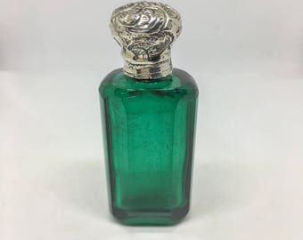 Victorian perfume bottle in green glass and silver cap.
