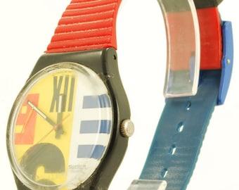 Swatch quartz wrist watch, black plastic cushion-shaped case, blue & red band