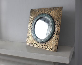 1930s Art Deco table mirror, brass and mosaic. Cutout square frame filigree leaf motif with a round mirror