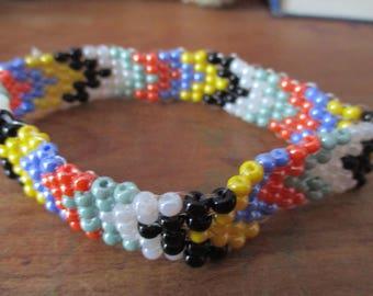 Woven black, white, blue, red, green, yellow stipe diagonal bracelet