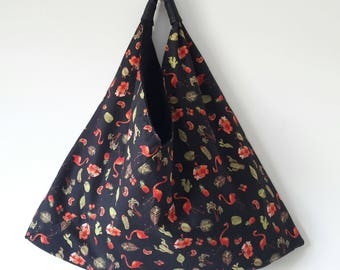 Reversible origami bag: a sober black face with raised dots and the other flamingos and cactus on a black background.