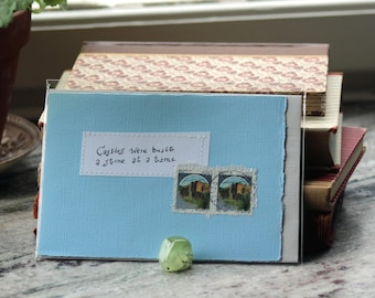 Castles were built a stone at a time Pale blue card with handwritten quote and Italian castle postal stamps