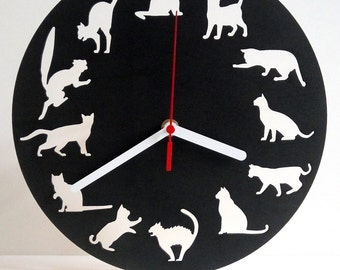 Wall clock with cut silhouettes of cats