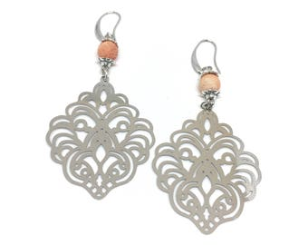 Dangle earrings filigree and orange frosted beads.