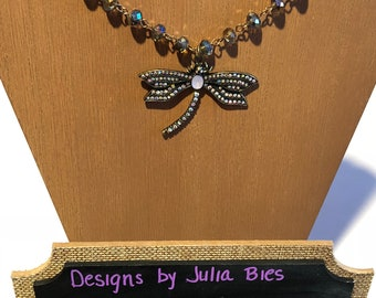 Iridescent purple-brown Swarovski style beaded necklace with an opalescent rhinestone accented dragonfly pendant