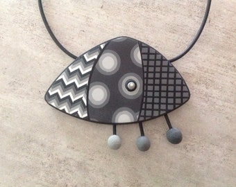 Pendant as a flying saucer in shades of grey polymer clay