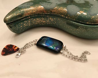Unique handcrafted art glass and sterling silver link bracelet .