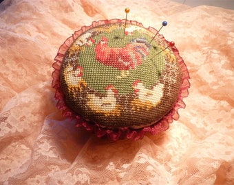 Embroidered cross stitch needle cushion.
