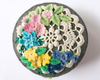 felt floral pincushion with a vintage style doily and lots of hand embroidery