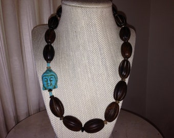 """21"""" Natural Burnt Horn carved oval bead necklace with a Turquoise Buddha head accent."""