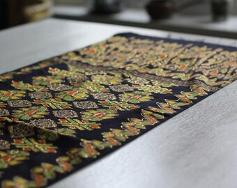 Black fabric with orange, yellow green and gold