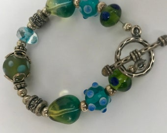 Glass beaded bracelet with sterling silver links and clasp.