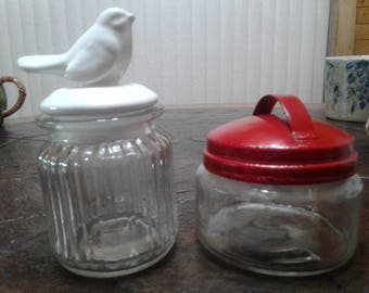 Two vintage jars one red topped one with a bird