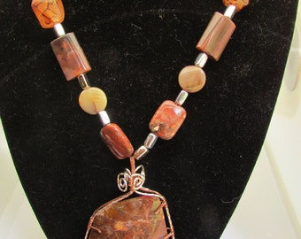 Necklace. Agate pendant center piece wire wrapper with copper and silver plate wire. Chain adorned with multi shape and size lapidary beads.