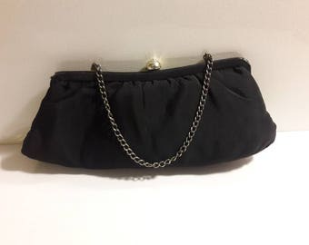 Black crepe clutch evening bag with champagne colored lining and jeweled tilt closure and chain