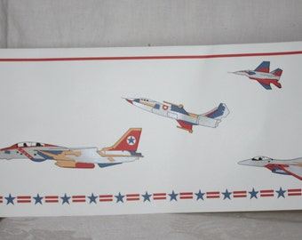 A new roll of wall paper border of different kinds of fighter jets, opened to photograph, 8 inches wide