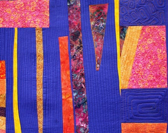 A contempory art quilt large geometric wall hanging in blue and orange