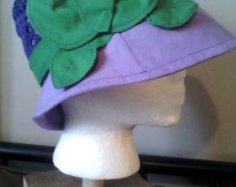 Violet ladies hat with emerald green leaf trim