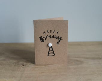 A7 Illustrated, typographic 'Happy Birthday' card with pom pom