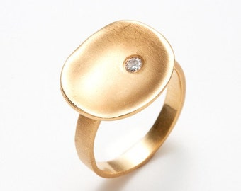concave 18K gold ring with a diamond