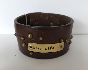 "Brown  leather decorative upcycled belt bracelet cuff with handstamped message in brass.  Message reads,""live life"""