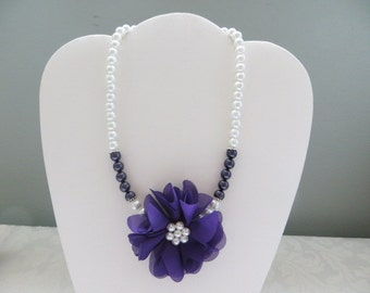 A Purple Floral Fabric Corsage With Purple And White Pearls Beaded Choker Necklace