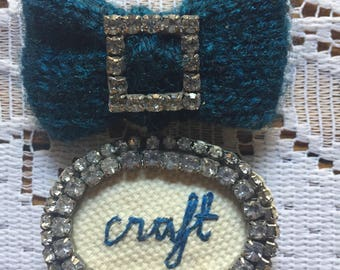 Navy knitted  bow brooch with diamante and embroidered 'craft'
