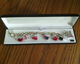 A Vtg New! Silver Tone Charm bracelet with a Variety of Charms.
