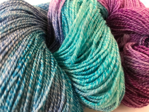 Hand dyed Merino and nylon sock yarn in cyan, emerald and magenta