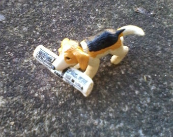 Miniature Bassett hound with newspaper in mouth