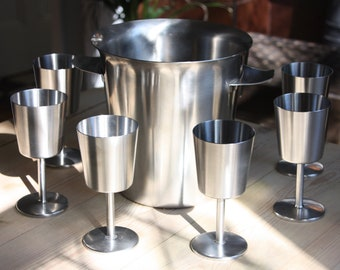 A Robert Welch stainless steel ice bucket and eight goblets made by Old Hall, 1960s.