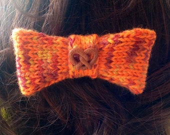 Hand-knitted bow hair pin with a pretzel adornment