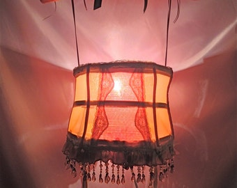 a Unique Tramp lamp crafted from a repurposed Sheer orange open girdle decorated in assorted flowers inside bottom and beads