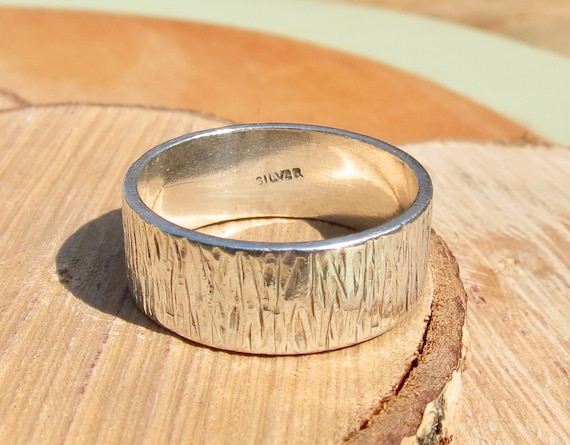 A silver ring with decorative wood bark design.