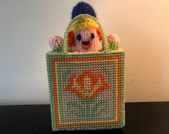 little knitted person in a small hand made bag