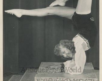 Smiling woman acrobat in extreme balance hand stand vintage photo
