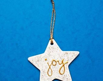 Gift ornament in white and gold with glitter and joy word.