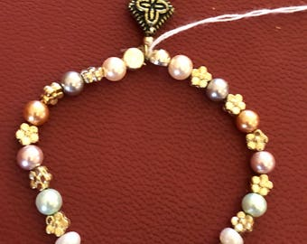 Beaded bracelet with a brass dangling charm