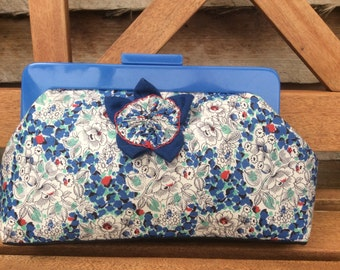 Hand made Blue floral clutch purse with blue resin handle, internal pocket and hand. made barkcloth fabric flower decoration.