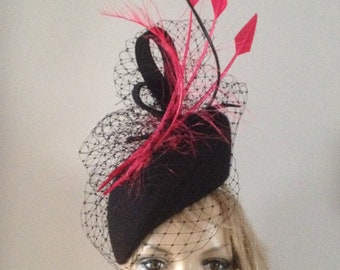 Black wool felt perching hat adorned with merry widow veiling dramatic fuchsia arrowhead and burnt ostrich feather details.